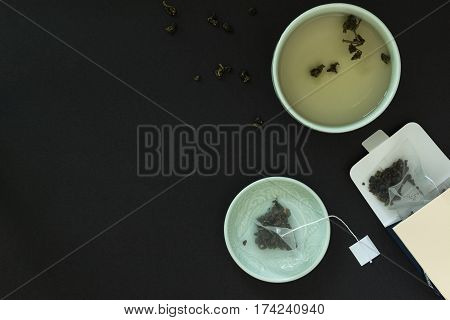 Japanese tea cup saucer with a bag of tea leaves and cardboard packaging on black background. Tea party.