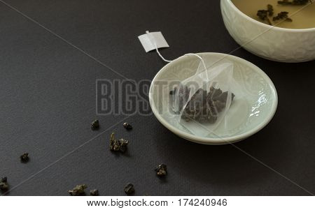 Tissue Tea bag with oolong in saucer on black background.