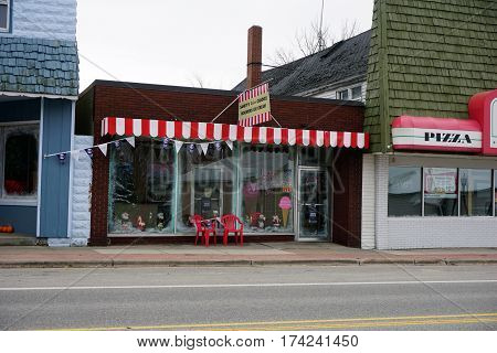 MANCELONA, MICHIGAN / UNITED STATES - NOVEMBER 27, 2016: One may eat Moomer's homemade ice cream, and drink fancy hot chocolate, at Sandy's Retro Candies store on State Street in downtown Mancelona.