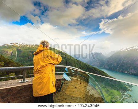 Tourism and travel. Male tourist nature photographer taking photo with camera enjoying Aurland fjord landscape from Stegastein lookout Norway Scandinavia.