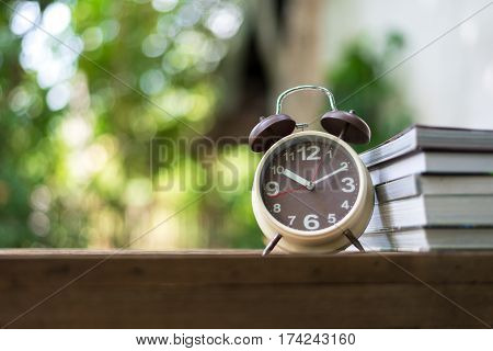 Retro alarm clock pointing on 10:00 o'clock with book or memo on wood table.