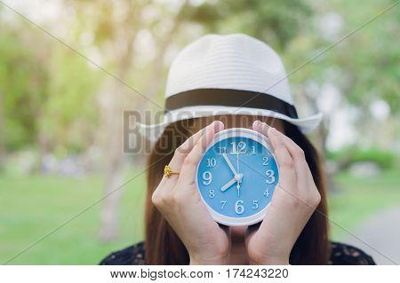 Asian woman holding alarm clock with time managementmacro alarm clock