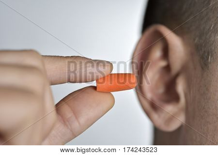 closeup of a young caucasian man inserting an orange earplug in his ear