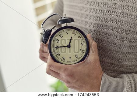 closeup of young Caucasian man winding or adjusting the time of an alarm clock