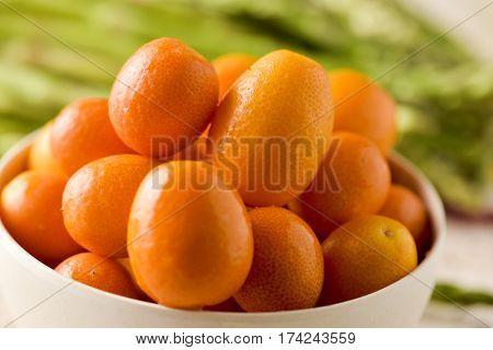closeup of some kumquat fruits in a white ceramic bowl