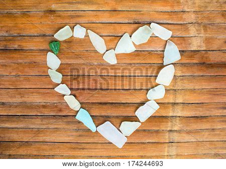Heart from sea glass on wooden background. Sea glass mosaic for St. Valentines Day. Shabby chic seaside decor on rustic wood board. Heart symbol photo for love and romance. Seashore banner template