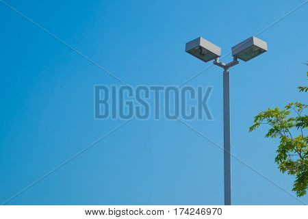 Lamp post electricity industry with blue sky background and tree. Spotlight tower against blue sky. street lamp. modern light pole.