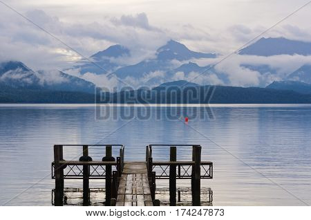 Pier on, mountains behind and clouds above  Lake Te Anau in the Fiordland National Park on the South Island of New Zealand