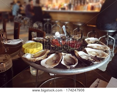 Oysters on ice plate served with lemon and sauce in the oyster bar.