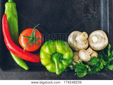 Group of fresh vegetables zucchini tomato bell pepper chili mushrooms greens for cooking easy vegetarian meals. A healthy way of life. Dark background top view. A copy of the places.