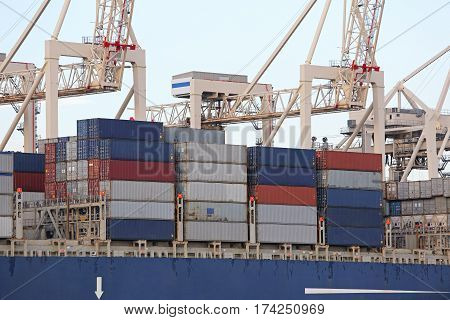 Three Pier Side Gantry Cranes Tower Over Container Ship