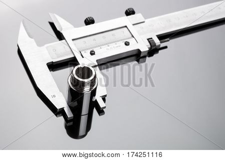 Caliper and cylindrical parts on a gray background