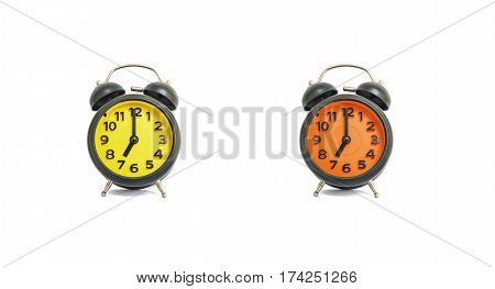 Closeup yellow alarm clock and orange alarm clock for decorate in 7 o'clock isolated on white background