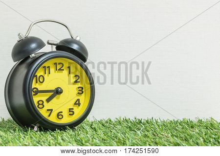 Closeup black and yellow alarm clock for decorate show a quarter to eight p.m. or 7:45 a.m. on green artificial grass floor and cream wallpaper textured background with copy space