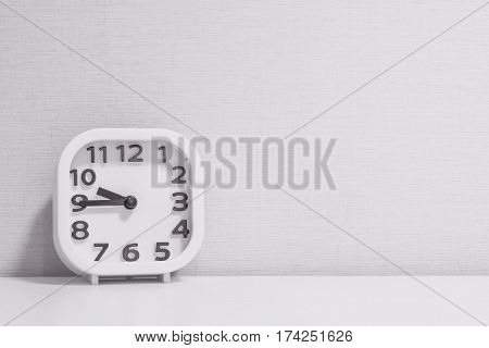 Closeup white clock for decorate show a quarter to ten p.m. or 9:45 a.m. on white wood desk and cream wallpaper textured background in black and white tone with copy space