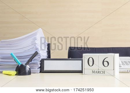 Closeup white wooden calendar with black 6 march word on blurred brown wood desk and wood wall textured background in office room view with copy space selective focus at the calendar