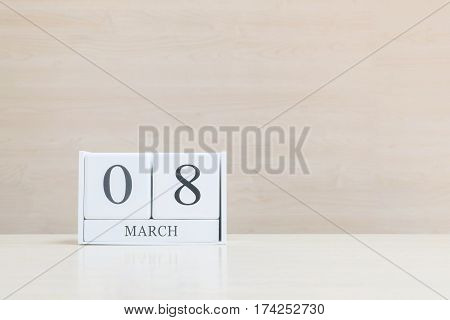 Closeup surface white wooden calendar with black 8 march word on blurred brown wood desk and wood wall textured background with copy space selective focus at the calendar