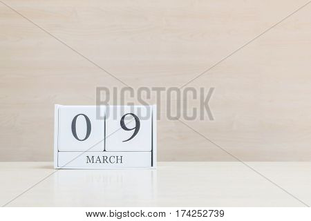 Closeup surface white wooden calendar with black 9 march word on blurred brown wood desk and wood wall textured background with copy space selective focus at the calendar