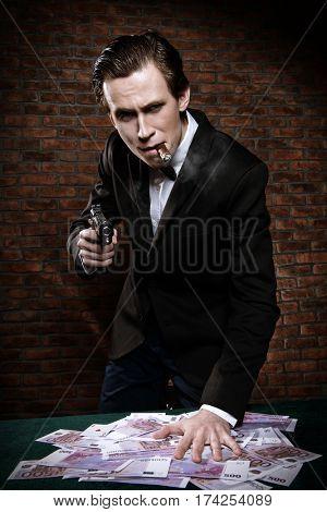 Cool gangster with a bunch of money threatens gun. Gambling industry, casino. Underworld concept.