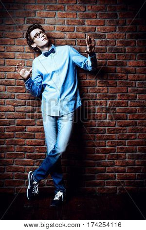 Emotional young man in jeans clothes and bow-tie posing by a brick wall. Men's beauty, fashion. Optics style. Copy space.
