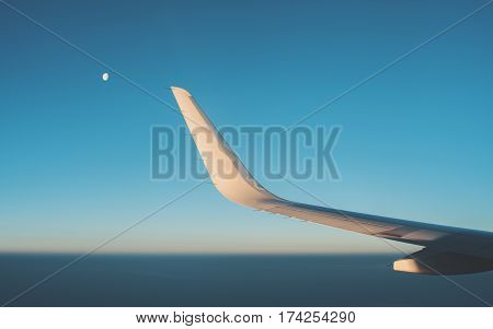 View from illuminator of dark teal morning misty horizon clear sky during dawn without clouds wing of modern airplane and partly closed moon