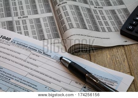 Tax preparation forms and tax tables US 1040 Tax form on wooden table for tax year 2016