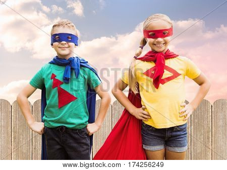 Two children wearing superhero costume standing with hands on hip against sky background