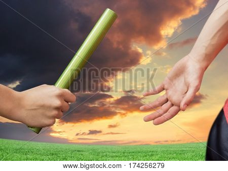 Digital composite of athlete passing the baton to teammate against dramatic sunset background