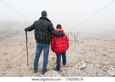 Concept of family escaping. Father and son in a mountain road with fog. Scene with actors