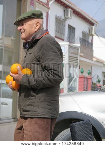 Alora Spain - Febuary 24 2017: Old man proudly carring his Orange crop in winter sunshine