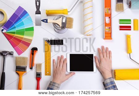 Decorator using a digital tablet. Color swatches and painting tools all around on table