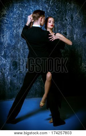 Beautiful passionate dancers dancing tango. Professional dancers. Couple in love dancing on a date. Love concept.