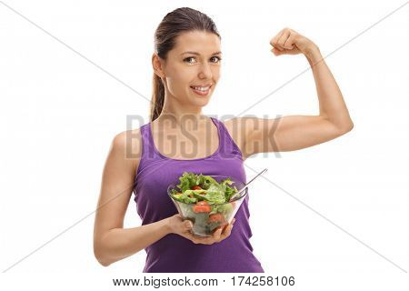 Young woman holding a salad and flexing her biceps isolated on white background