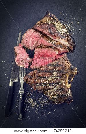 Barbecue dry aged Cote de Boeuf as close-up on a black slate