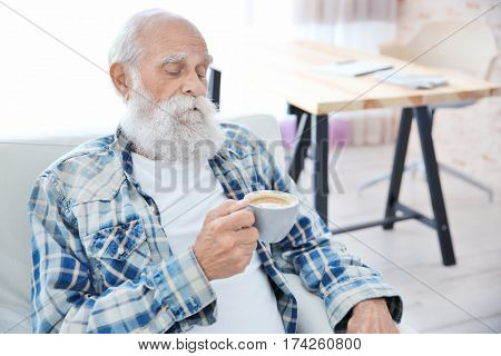 Senior man with cup of coffee sitting in arm chair