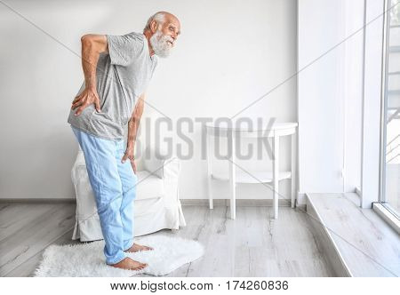 Senior man with pain in back trying to stand up