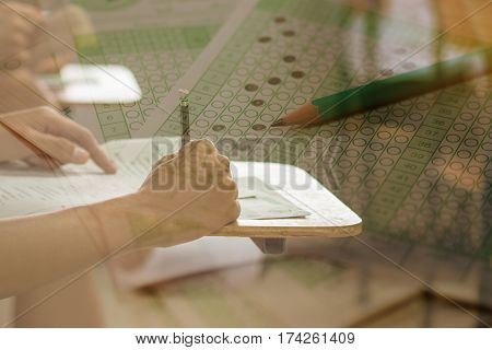 double exposure of students writing a test in their exercise and exam multi-choice in classroom