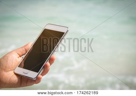 taking picture by smart phone selfie on blurred beautiful at beach background Vacation concept