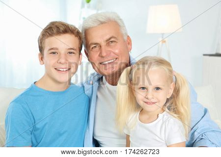 Cute children with grandfather sitting on sofa in living room