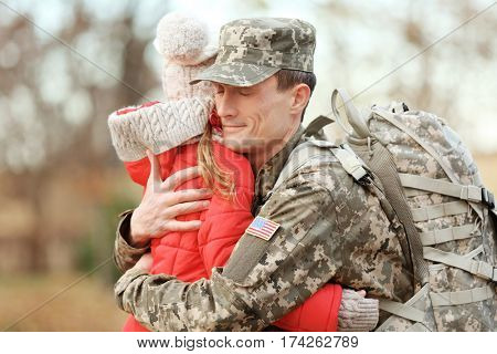 Soldier in camouflage hugging daughter outdoors