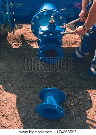 Worker Hands Screwing Gate Valve With Nuts On Piping.