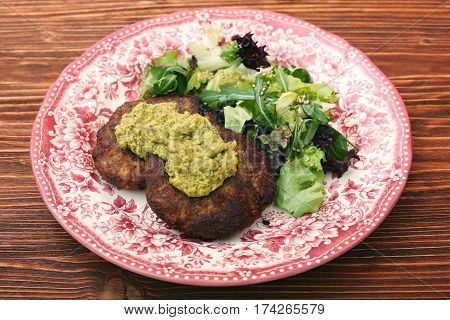 Fried beef patties with pesto sauce and greens. Healthy eating concept.