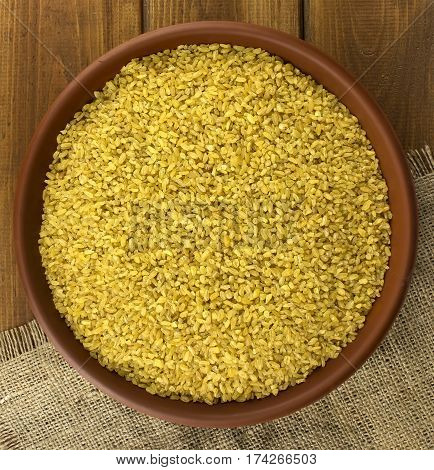 Dry bulgur wheat in a clay bowl on the table and sacking