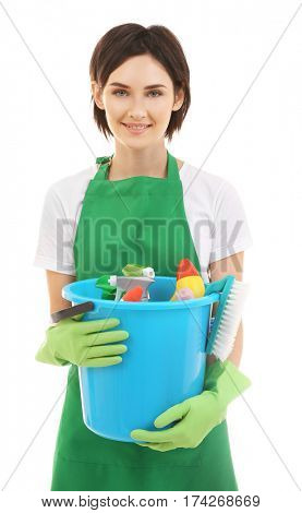 Young woman holding bucket with cleaning supplies on white background
