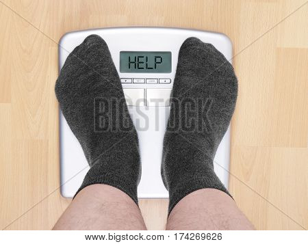 overweight man on personal scales, display reads help