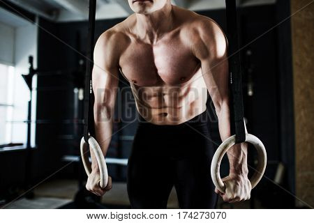 Intense workout in dark gym: closeup shot of ripped male torso with defined muscle pattern on chest and arms during gymnastic rings exercise