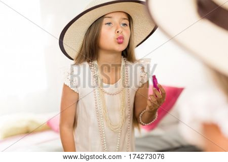 Mirror reflection shot of little girl playing dress up in mothers jewels and hat putting makeup and pink lipstick on, blowing air kisses and grimacing