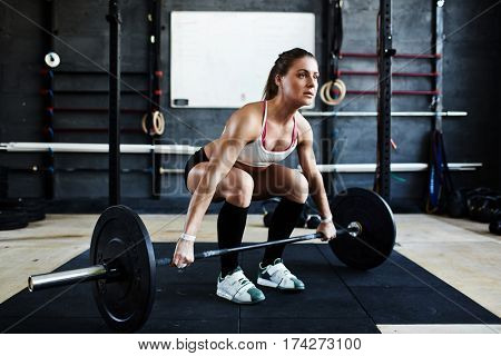 Intense workout in dark gym: bodybuilder woman ready to pick up heavy barbell with effort standing in squatting stance