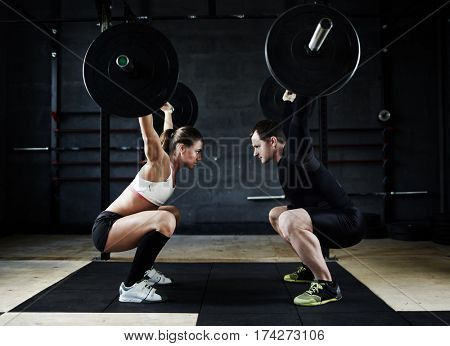 Motivational side view image of young man and woman performing overhead squats with huge heavy barbells looking at each other