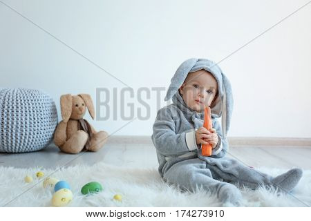 Cute little baby in bunny costume  sitting on furry rug